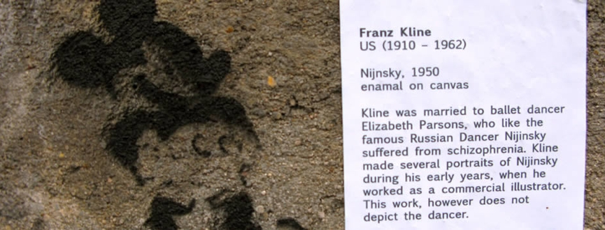 Mickey Mouse graffiti on streets in Paris, labeled with text labels from Met exhibition of american painters. This label refers to artist Franz Kline
