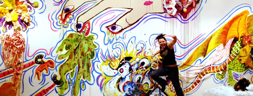 Artist leaping in front of a installation of her interactive and collaborative exhibition WYSIWYG in Minnesota
