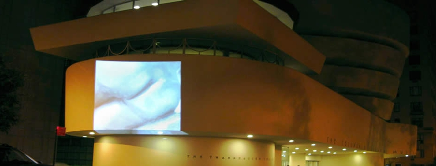 Projection of a video of the behinds of Roman sculptures projected on the side of the Guggenheim Museum