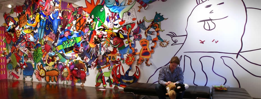Interactive mural of bright collaborative creatures that the audience can add to on wall in Houston Texas gallery