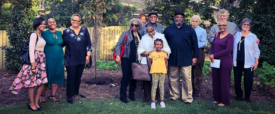 Members of the family of Ned Cobb stand with white oak tree planted in his honor