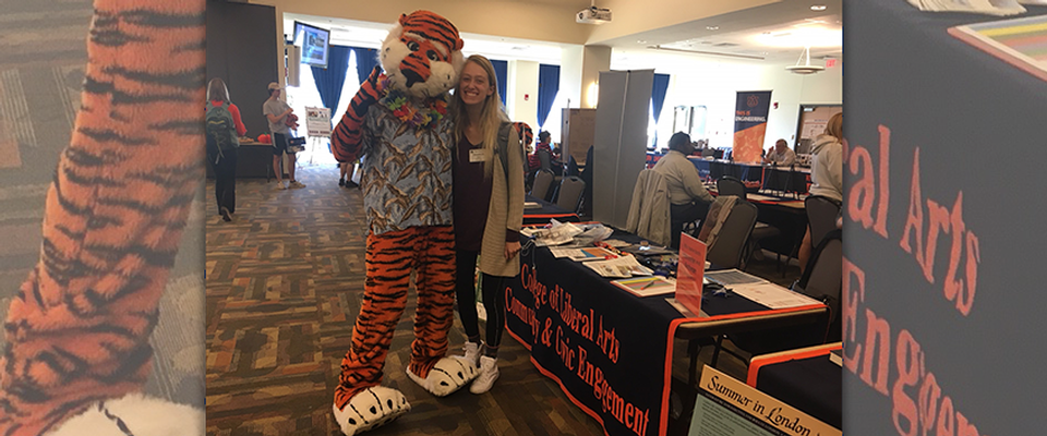 This picture is of Aubie and a College of Liberal Arts Student standing in front of the CCE booth at the fall 2017 study abroad fair.