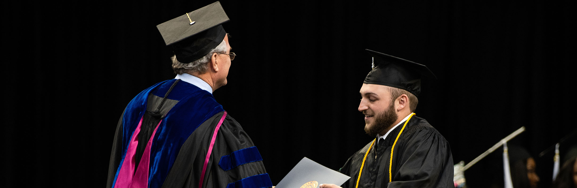 Dean Joe Aistrup hands a student his diploma on stage at graduation