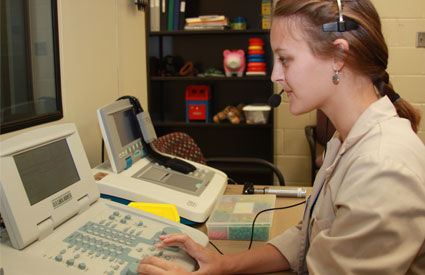Audiology student working with equipment