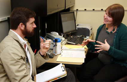 An audiology student and Kelli Watts discuss a patient's case.