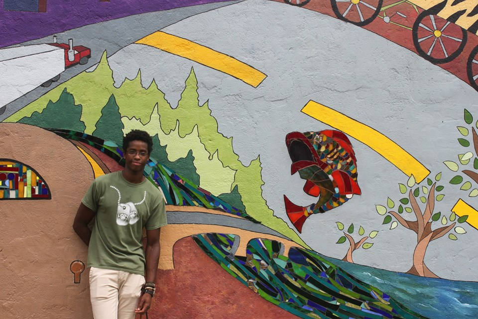 image of Living Democracy student Jelani Moore in front of Elba's community mural