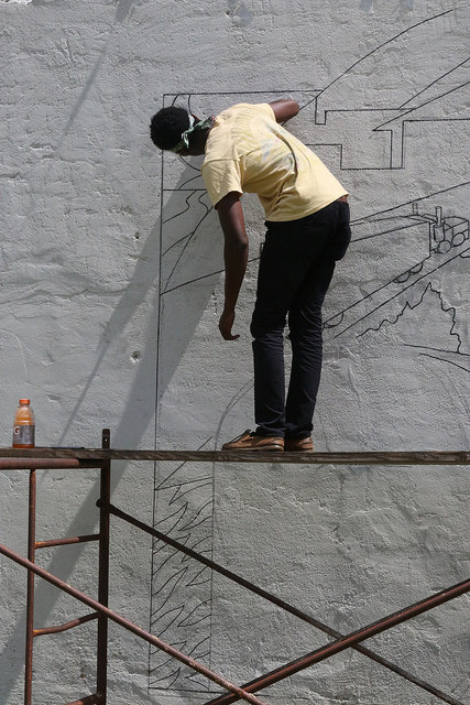 image of Living Democracy Student Jelani Moore working on mural