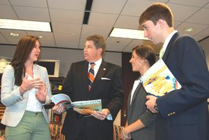 Auburn University students Lowery McNeal, Cristiana Shipma and Blake Evans present Jim Byard, director of the Alabama Department of Economic and Community Development, a copy of the Living Democracy magazine. (Photo by Jim Plott)