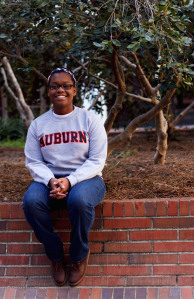 Sitting on a red brick retaining wall, Taryn smiles brightly in her Auburn University sweatshirt.