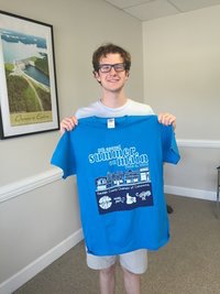 Weston Sims holding a Summer on Main tee shirt