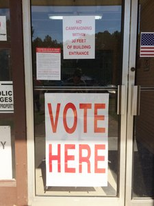 "Door to store with a sign saying ""Vote Here"""