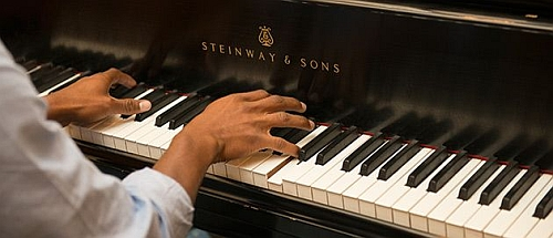 Hands playing a Steinway piano