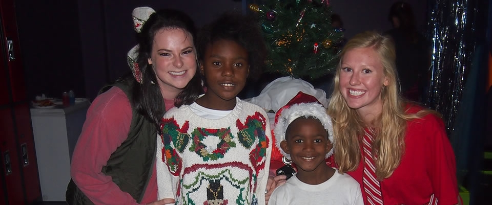 Two volunteers with 2 children dressed in Christmas attire