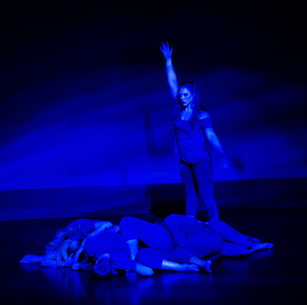 Dancers in pile on floor; dancer standing above; dark background