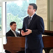 man singing in front of accompanist on piano